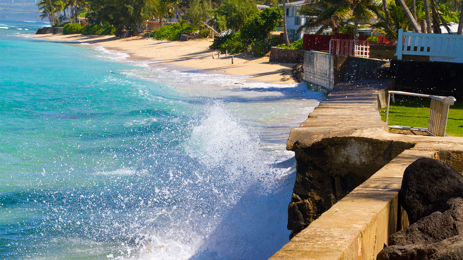 A wave crashing against a seawall in Hawai'i